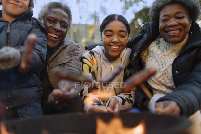 Happy grandparents and grandchildren roasting hot dogs over campfire — Stock Photo