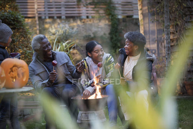 Happy grandparents and granddaughter at autumn campfire — Stock Photo
