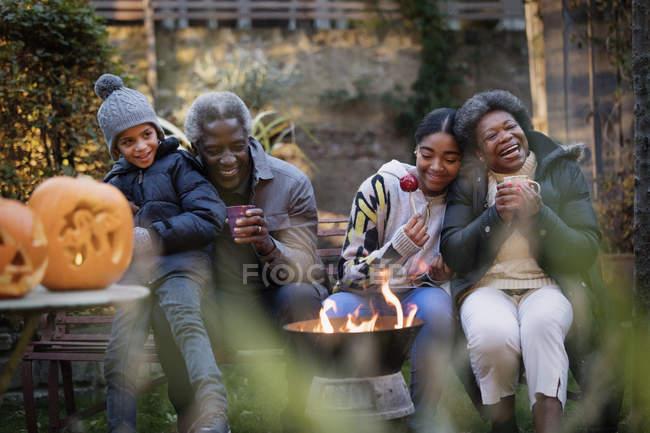 Abuelos y nietos disfrutar otoño fogata de patio trasero - foto de stock