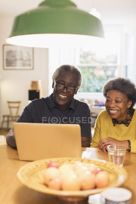 Happy senior couple using laptop in kitchen — Stock Photo
