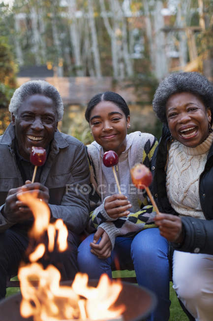 Портрет улыбается, счастливые бабушка с дедушкой и внучка наслаждаются сладкими яблоками у костра — стоковое фото