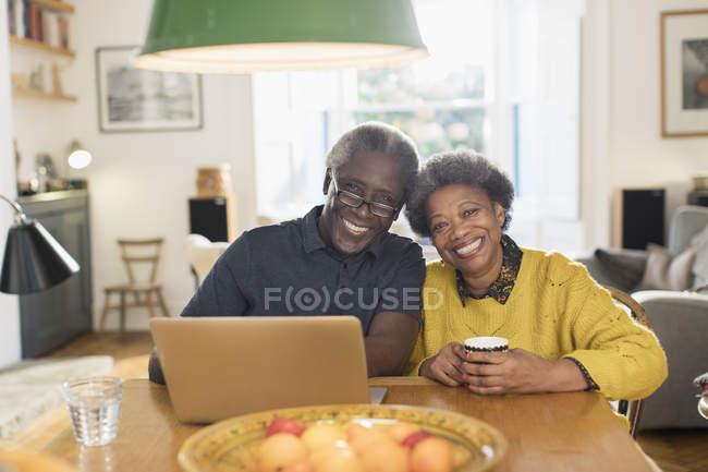 Ritratto sorridente, coppia anziana fiduciosa utilizzando il computer portatile al tavolo da pranzo — Foto stock