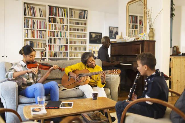 Abuelos y nietos tocando instrumentos musicales en la sala de estar - foto de stock
