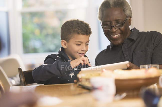 Grand-père et petit-fils utilisant une tablette numérique — Photo de stock