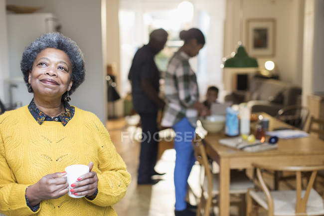 Smiling, satisfied senior woman drinking coffee with family in background — Stock Photo