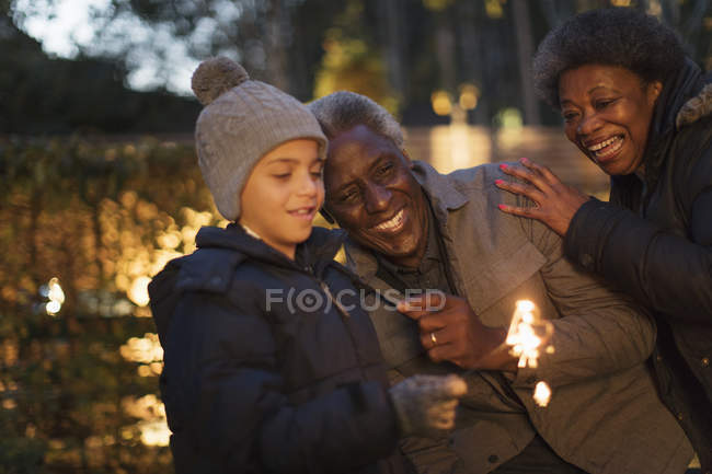 Grandparents and grandson playing with firework sparkler — Stock Photo