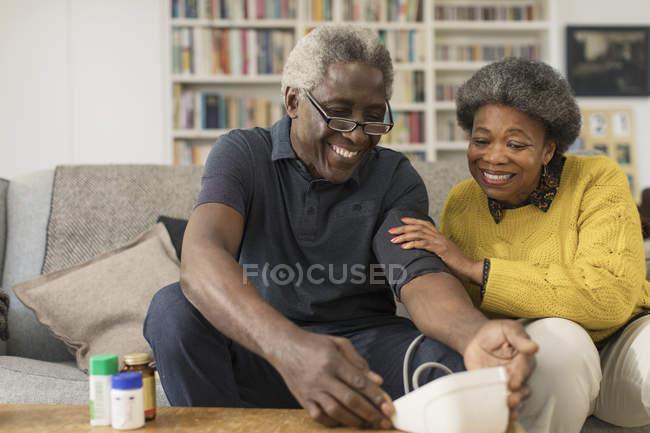 Lächelndes Senioren-Paar überprüft Blutdruck — Stockfoto