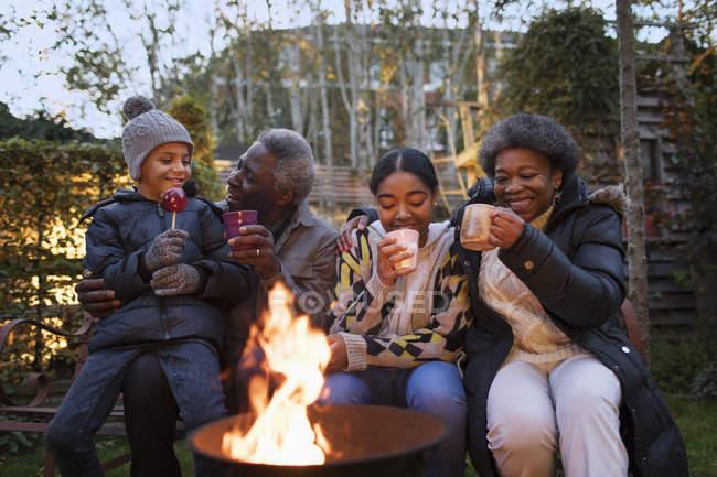 Бабушки и дедушки и внуки, пить горячий какао на костре — стоковое фото