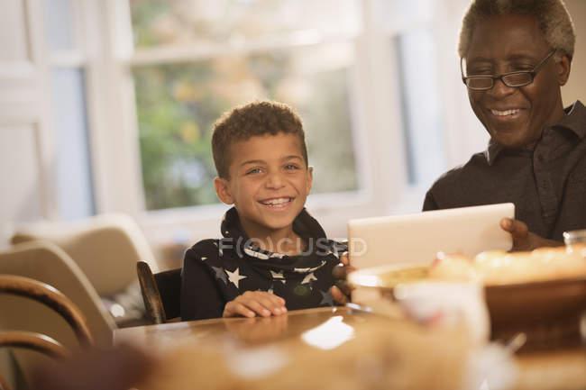 Portrait petit-fils souriant utilisant une tablette numérique avec grand-père — Photo de stock