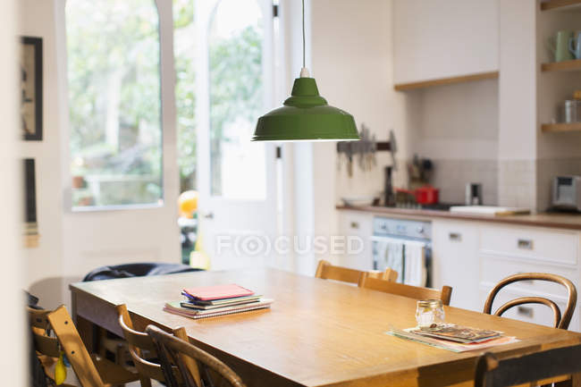 Green pendant light hanging over dining table — Stock Photo