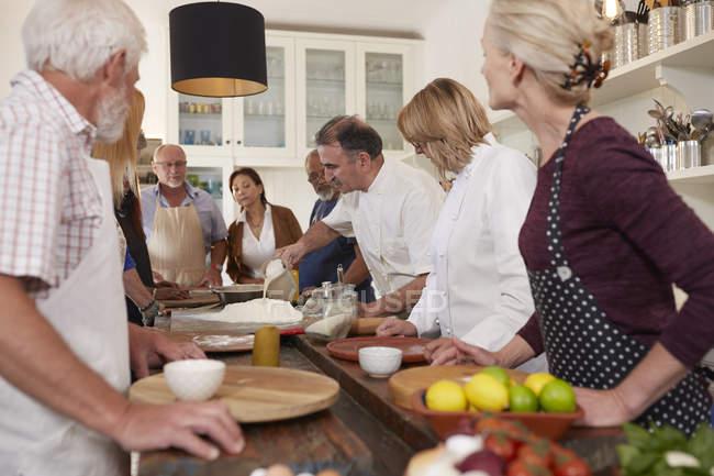 Активних старшим друзів перегляду шеф-кухаря в піци приготування їжі клас — стокове фото