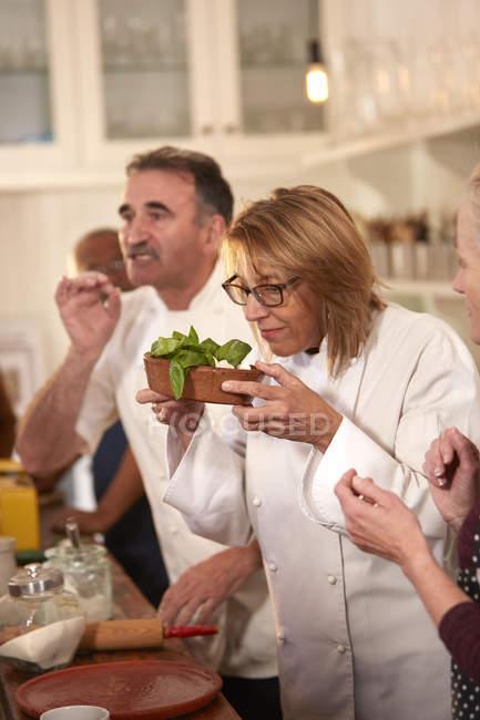 Шеф-повар нюхает свежий базилик в кулинарном классе — стоковое фото