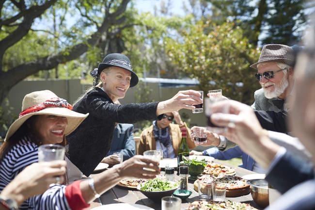 Amigos seniores felizes brindando copos de vinho na mesa de festa ensolarada jardim — Fotografia de Stock