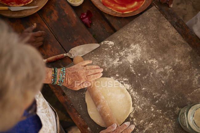 Vista aérea mujer mayor rodando, haciendo masa de pizza fresca - foto de stock