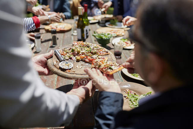 Friends sharing homemade pizza at sunny patio table — Stock Photo