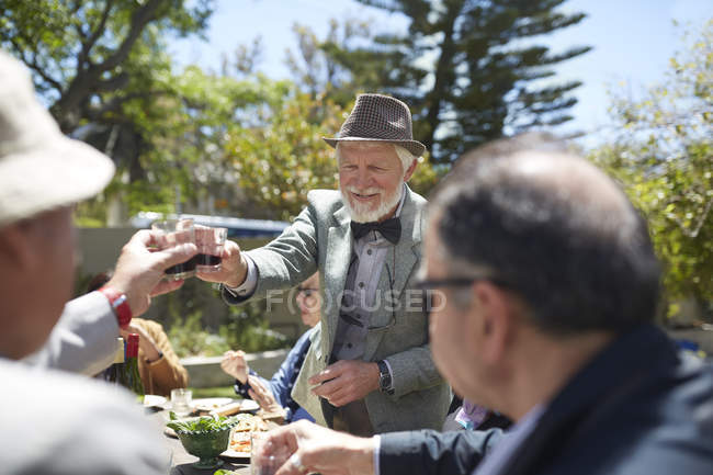 Senior man in suit and bow tie toasting friends with wine at sunny garden party — Stock Photo