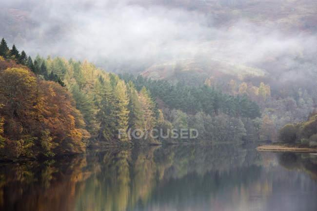 Geheimnisvoller Nebel über ruhige Herbst Bäume und See, Loch Pitlorchy, Pitlochry, Schottland — Stockfoto