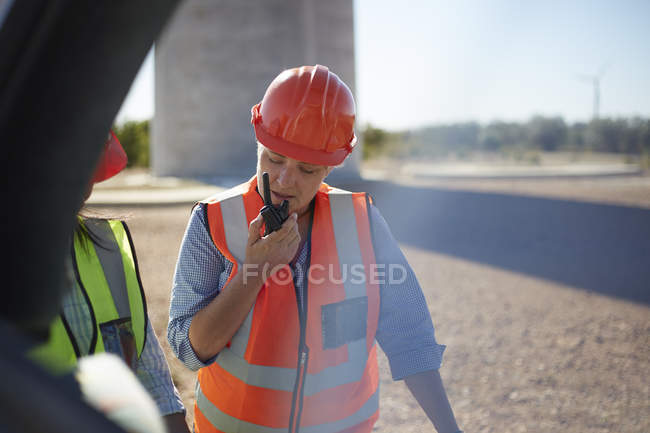 Female worker using walkie-talkie at power plant — Stock Photo