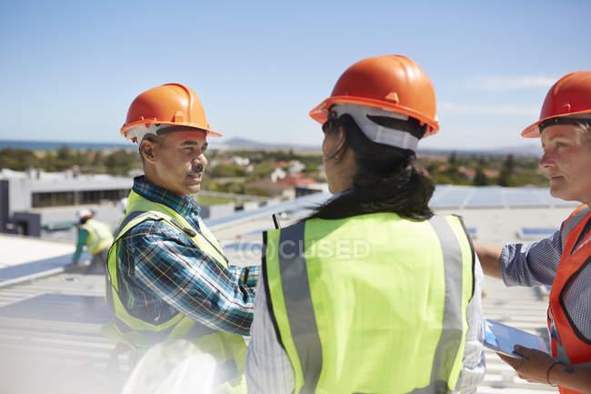 Рабочие разговаривают на солнечной электростанции — стоковое фото