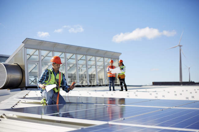 Engineer testing solar panels at sunny power plant — Stock Photo