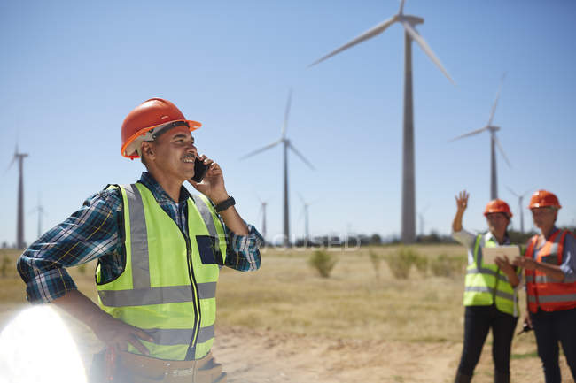 Smiling engineer talking on cell phone at sunny wind turbine power plant — Stock Photo