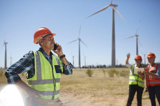 Улыбаясь инженер говорить на мобильный телефон на Солнечный ветер турбины электростанции — стоковое фото