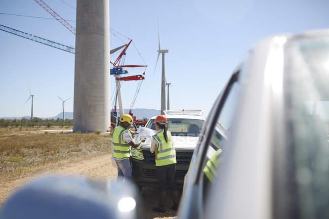 Инженеры, обзор чертежи на Ветер турбины электростанции — стоковое фото
