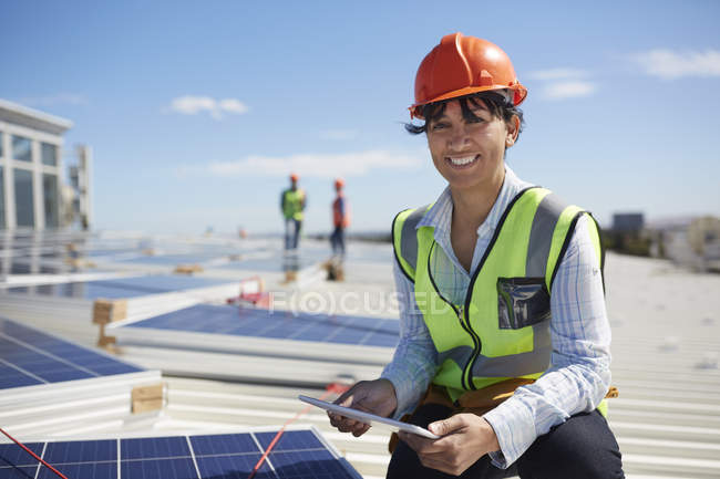 Portrait smiling, confident female engineer with digital tablet inspecting solar panels at sunny power plant — Stockfoto