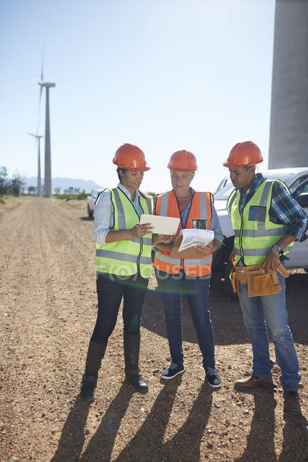 Engineer and workers using digital tablet at wind turbine power plant — Stock Photo