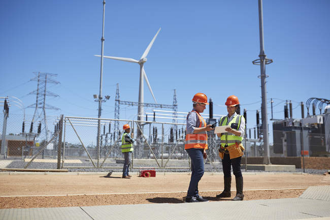 Engineers using digital tablet at sunny wind turbine power plant — Stock Photo