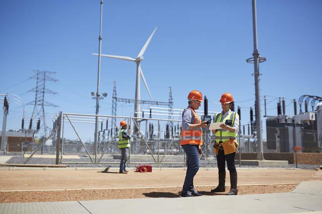 Инженеры, с помощью цифрового планшета на Солнечный ветер турбины электростанции — стоковое фото