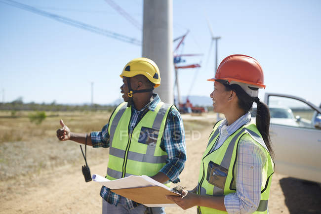 Engineers with blueprints talking at sunny power plant — Stock Photo