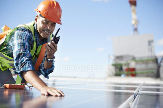 Engineer with walkie-talkie inspecting solar panel at power plant — Stock Photo