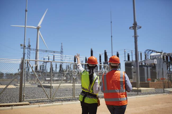 Рабочие, наблюдая ветровой турбины на электростанции — стоковое фото