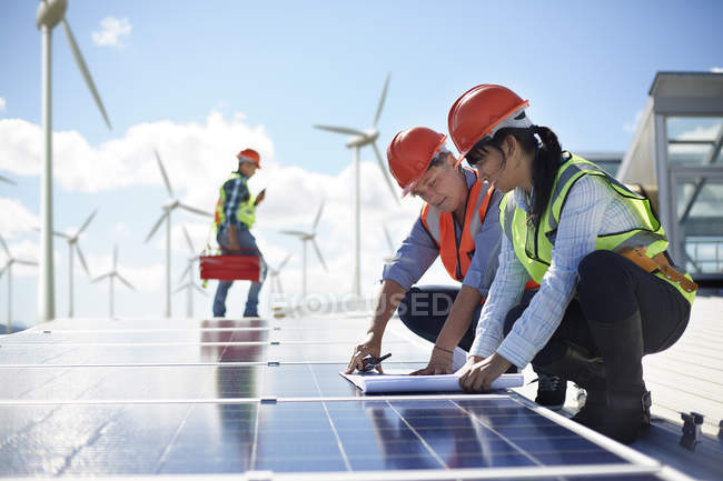 Engineers reviewing blueprints at solar panel at power plant — Stock Photo
