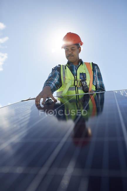 Engineer examining solar panel at sunny power plant — Stock Photo