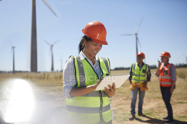 Smiling engineer using digital tablet at sunny power plant — Stock Photo