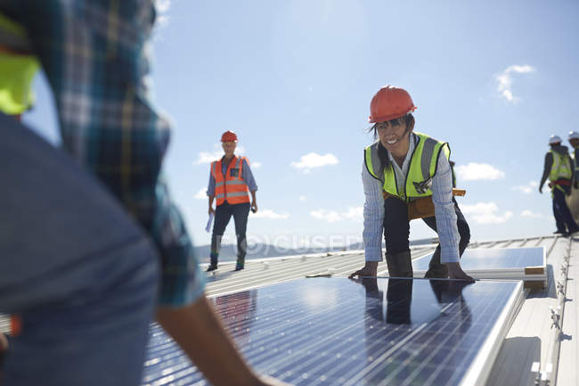 Engineers lifting solar panel at sunny power plant — Stock Photo