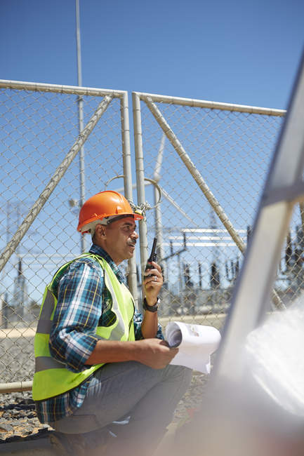 Engineer with walkie-talkie at sunny power plant — Stock Photo