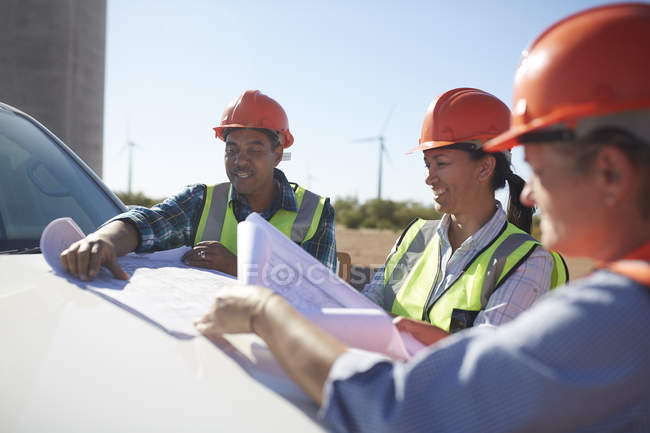 Engineers reviewing blueprints on truck at sunny wind turbine power plant — Stock Photo