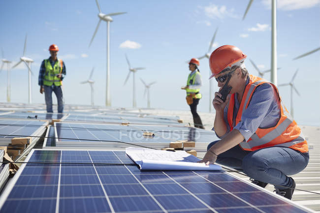 Engineer with walkie-talkie and blueprint at solar panel at sunny power plant — Stock Photo