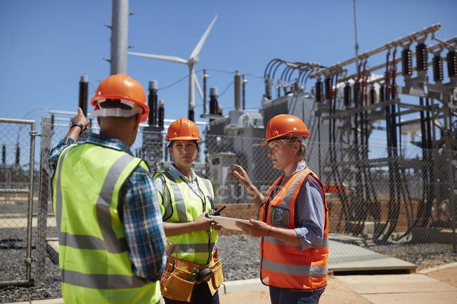 Engineers with digital tablet at sunny power plant — Stock Photo