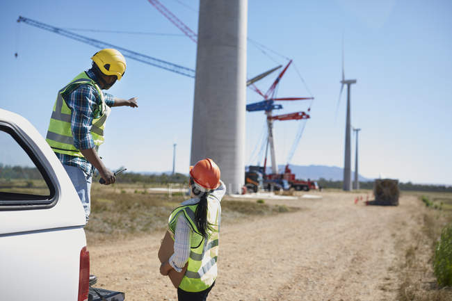 Engineers on dirt road at wind turbine power plant — Stock Photo