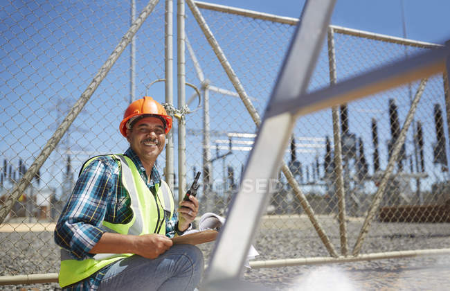 Portrait smiling, confident male engineer with walkie-talkie at power plant — Stock Photo