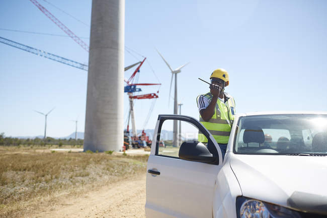Engineer using walkie-talkie at truck at sunny wind turbine power plant — Stock Photo