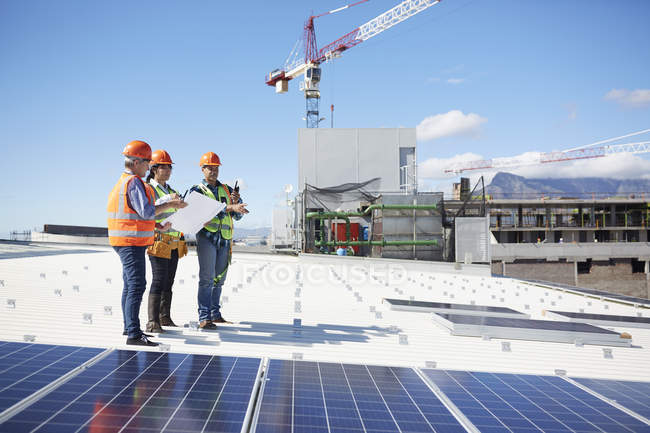 Engineers with blueprint at solar panels at sunny power plant — Stock Photo