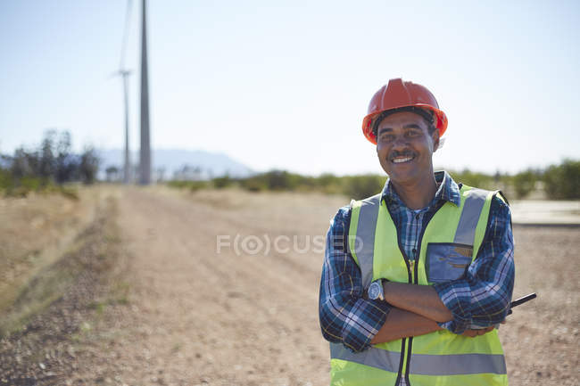Portrait smiling engineer on dirt road at wind turbine power plant — Stock Photo