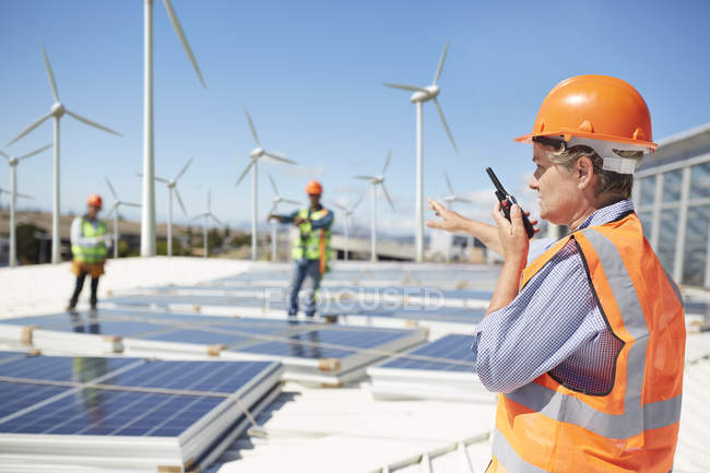 Female engineer using walkie-talkie at alternative energy power plant — Stock Photo