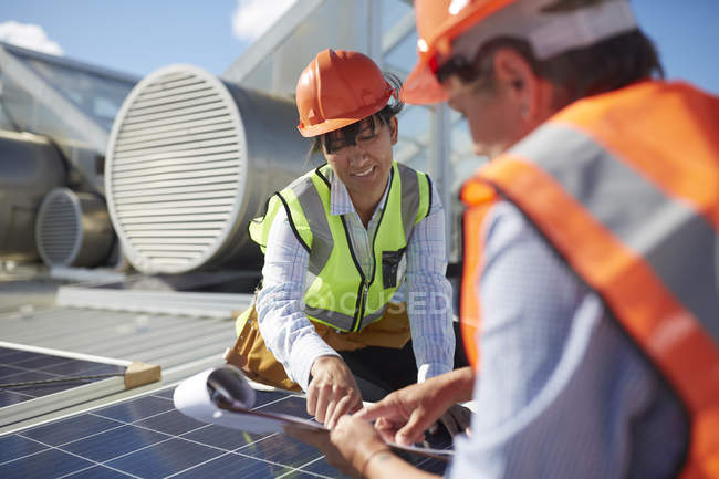 Engineers with clipboard examining solar panel at sunny power plant — Stock Photo