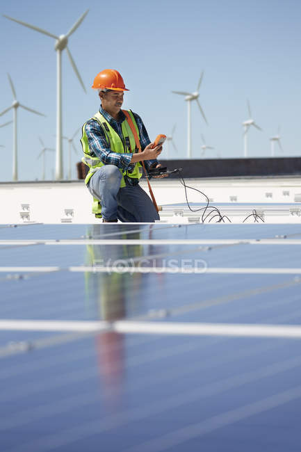 Engineer with equipment inspecting solar panels at sunny power plant — Stock Photo